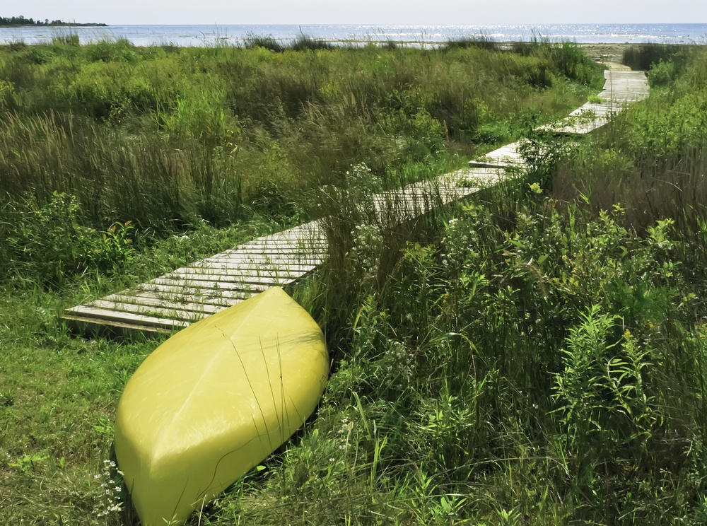 Yellow kayak, upside down, at end of boardwalk to beach
